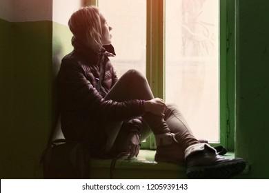 Sad, thoughtful woman sitting on the window sill.