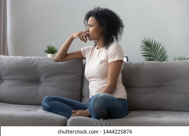 Sad thoughtful worried african american girl sit on sofa looking away feel depressed doubtful, lonely stressed upset young black girl thinking of psychological problem thinking regret about mistake