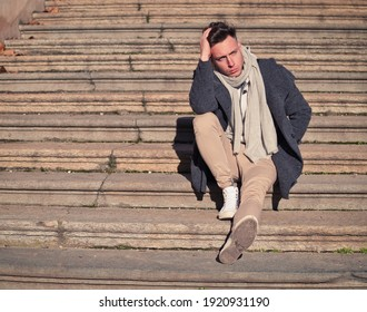 Sad, thoughtful young man outdoor wearing coat, scarf and shirt sitting on stone stairs outside