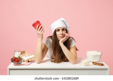 Sad tired chef cook confectioner or baker in apron white t-shirt, toque chefs hat sit at table with paper cup of coffee isolated on pink pastel background in studio. Mock up copy space food concept