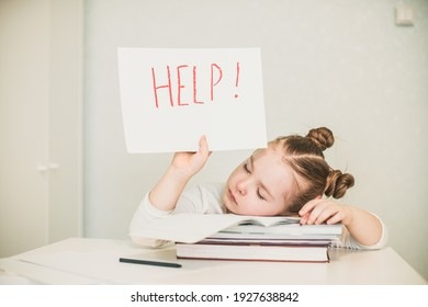 Sad tired frustrated girl sitting at the table with many books and holding paper with word Help. Learning difficulties. High quality photo