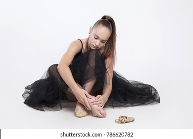 Sad and tired girl gymnast, sitting on the floor. Dancer touching her foot. Isolated on white background