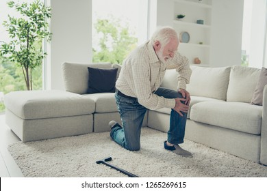 Sad tired stylish old man wearing checked shirt on carpet touching leaning on knee painful disease broken joint in white light modern interior