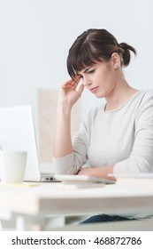 Sad tired woman having a bad headache, she is sitting at office desk and touching her temple