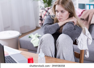 Sad and tired woman with PPD working beside table, looking on laptop, sitting in messy room