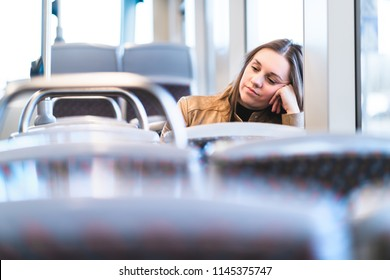 Sad tired woman in train or bus. Bored or unhappy passenger sitting in tram leaning against hand. Upset lady on a late delayed bus. Negative public transportation concept.
