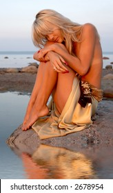 sad topless girl sitting on the rock with water reflection