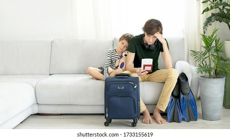 Sad tourists, teen and child, with a suitcase, tickets and flippers stays at home during the coronavirus pandemic. Cancellation of leave and closing of borders between countries. End of quarantine.
