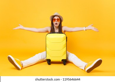 Sad traveler tourist woman in summer casual clothes, hat sit near suitcase isolated on yellow orange background. Female passenger traveling abroad to travel on weekends getaway. Air flight concept