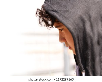 Sad troubled school boy teenager wearing a hoodie posing and thinking in his own thoughts - close up stock photo with copy space for writing