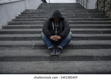 Sad troubled teenager school boy with hood on posing outdoor sitting alone. Depression, social isolation, loneliness, mental health and discrimination concept.