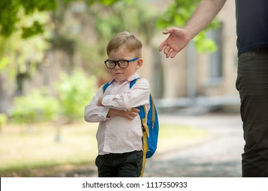 Sad and unhappy child with backpack and parent hand. Upset toddler boy. problem child. concept for bullying, depression stress or frustration. On school background. Back to school