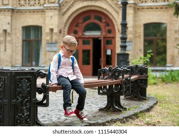 Sad and unhappy child with backpack. Upset toddler boy. problem child. concept for bullying, depression stress or frustration. On school background. Education for small kids. Back to school