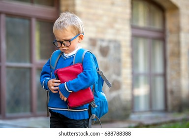 Sad and unhappy child with book in hands and backpack. Upset toddler boy. problem child. concept for bullying, depression stress or frustration. On school background. Education for small kids.