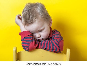 sad and unhappy child on small chair. Upset toddler boy. problem child with head in hands. concept for bullying, depression stress or frustration. On yellow background. Space for text.
