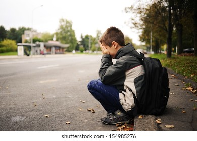 sad and unhappy child in the street