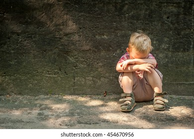 sad and unhappy child in the street. Upset problem child with head in hands sitting on staircase concept for bullying, depression stress or frustration. concrete wall as  background