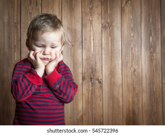 sad and unhappy child. Upset toddler boy. problem child with head in hands. concept for bullying, depression stress or frustration. On wooden background. Space for text.