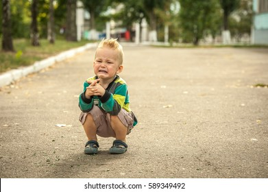 sad and unhappy child. Upset toddler boy. problem child with head in hands. concept for bullying, depression stress or frustration. Space for text.