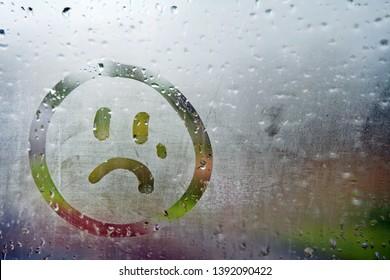 Sad unhappy face drawn on fogged glass on a wet rainy grey window soft light grey skies