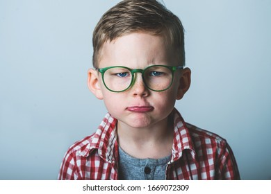 Sad and unhappy school boy. Portrait of child in glasses. Face