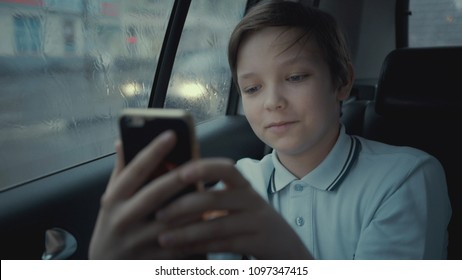 Sad, unhappy young boy riding in car through city during rainy day, using social network on his smartphone.