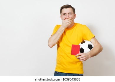 Sad upset crying shocked young man, football fan or player in yellow uniform cover mouth by hand hold red soccer card for retire from field isolated on white background. Sport play, lifestyle concept