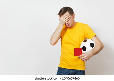 Sad upset crying shocked young man, football fan or player in yellow uniform cover eyes by hand, hold red soccer card for retire from field isolated on white background. Sport play, lifestyle concept