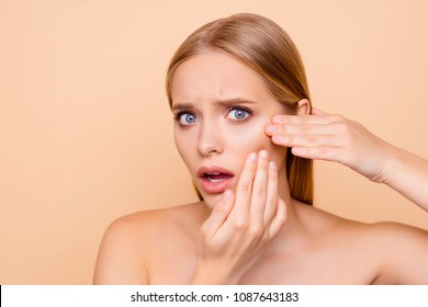 Sad, upset, frustrated, disappointed, nude, natural girl touching cheek with fingers having dry oiled skin, minerals, vitamins, detox, moisturizing, hydration concept isolated on beige background