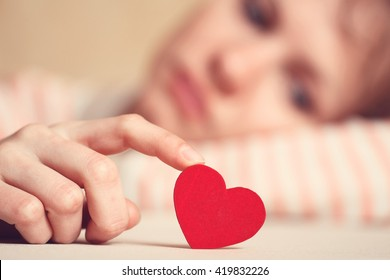 Sad and upset girl is touching heart symbol with finger and looking at it. Woman is thinking about unrequited love and relations difficulties. Focus is on heart. Love and relationships concept