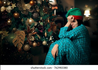 Sad Upset Lonely Girl Crying Next to Her Christmas Tree. Depressed woman in tears having an emotional moment on holidays
