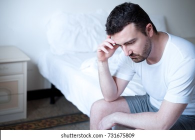 Sad and upset man waking up in the morning light