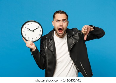 Sad upset stylish young unshaven man in black leather jacket white t-shirt holding round clock isolated on blue wall background studio portrait. People lifestyle concept. Hurry up. Mock up copy space