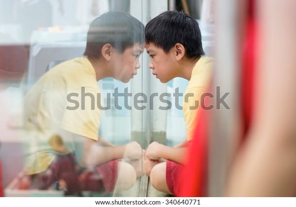 Sad upset waiting boring depressed child (boy) near a window, reflection.