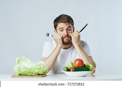 a sad vegetarian looks at vegetables on a light background, eating restrictions