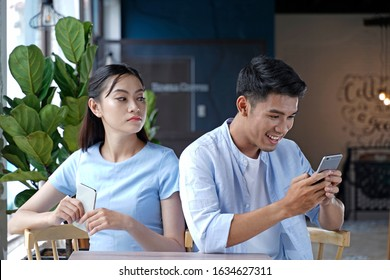 sad view of young married couple using their mobile phone in bed ignoring each other as strangers in relationship and communication problems