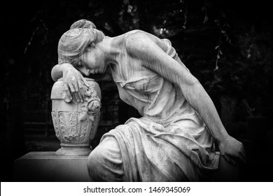 Sad and weeping woman sculpture. Sad grieving expression sculpture with sorrow face down thinking crying. Black and white BW photography.