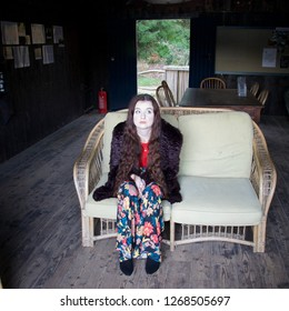 A sad, white faced, fashionably dressed lady with long brunette hair sits forlornly on a wicker sofa in a summerhouse