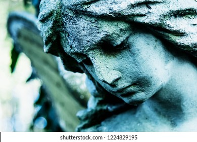 Sad winged angel at an old cemetery. Vintage styled image of ancient statue. Fragment of sculpture. (religion, faith, death, resurrection, eternity concept)
