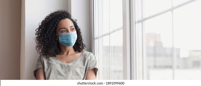 Traurige Frau allein während der Koronavirus-Pandemie tragen Gesichtsmaske im Haus für soziale Distanzierung. Mixed Rennen Mädchen, das Fenster, Banner anschaut