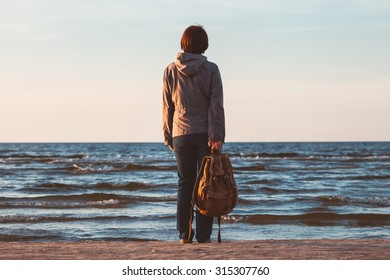 Sad woman with backpack looking to sea at sunset.
