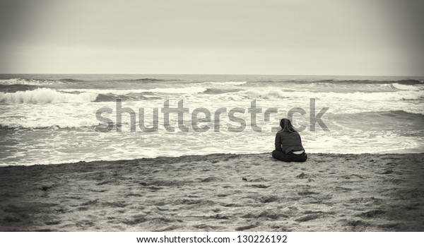 Sad woman at the beach in sepia colors.