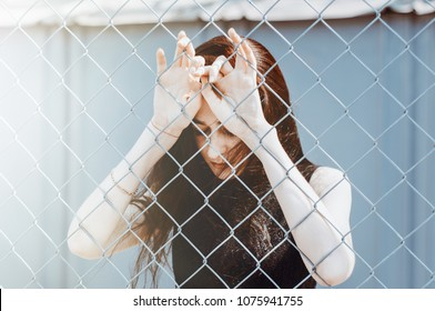Sad woman behind the fence. Girl hiding her face behind hands. She is crying. Black and white photo. Sadness, depression, loneliness and disappointment. Problems and pain. Social, family problems.
