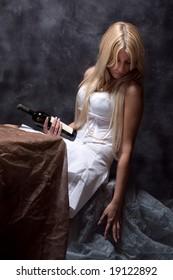 sad woman with bottle of wine, studio dark