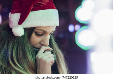 Sad woman by the christmas tree contemplating. Lonely Christmas woman on the winter street at night. Festive brunette feeling sad at christmas looking up.christmas stress with tree in background