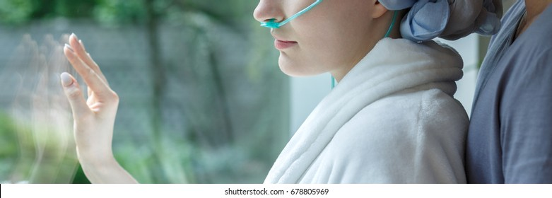 Sad woman with cancer looking through hospital window