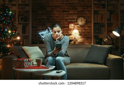 Sad woman celebrating Christmas at home alone: she is sitting on the sofa and waiting for messages on her smartphone