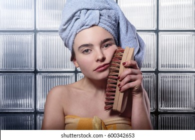 sad woman cleaning her face with a huge scrubbing brush