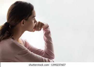 Sad woman close up side view pose aside copy space for text, girl holds hand near mouth indecision posture, feels uncertain nervous difficult to make decision, unwanted pregnancy and abortion concept