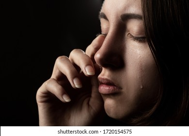 sad woman with closed eyes crying, on black background, closeup portrait, side view